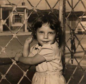 Uma fotografia antiga de uma menina de cerca de quatro anos. Ela tem os cabelos lisos e curtos e usa um vestido branco.